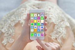 Telefono della tenuta del vestito dall'oro della donna con i apps delle icone dello schermo domestico fotografie stock libere da diritti