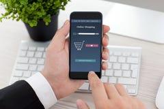 Telefono della tenuta dell'uomo d'affari con il app online sullo schermo Fotografia Stock