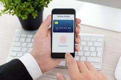 Telefono della tenuta dell'uomo d'affari con l'impronta digitale per acquisto online Immagine Stock