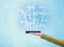 Telefono della tenuta della mano con i numeri digitali Fotografie Stock