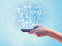 Telefono della tenuta della mano con i numeri digitali Fotografia Stock