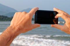 Telefono della tenuta della mano dell'uomo horizontaly Immagini Stock
