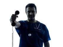 Telefono della tenuta della siluetta dell'uomo di medico Immagini Stock