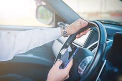 Telefono della tenuta e dell'uomo d'affari in automobile Immagini Stock
