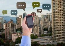 Telefono della tenuta ed icone della bolla di chiacchierata sopra la città Fotografia Stock Libera da Diritti