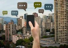 Telefono della tenuta ed icone della bolla di chiacchierata sopra la città Immagine Stock
