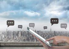 Telefono della tenuta ed icone della bolla di chiacchierata sopra la città Immagini Stock Libere da Diritti