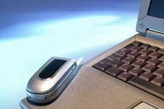 Telefono delle cellule sul computer portatile di affari sopra spazio blu aperto Fotografie Stock