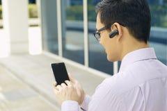 Telefono di Calling On Mobile dell'uomo d'affari con Bluetooth mani libere immagine stock