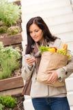 Telefono di compera delle verdure delle drogherie della tenuta della giovane donna Fotografie Stock Libere da Diritti