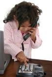 Telefono di composizione della bambina allo scrittorio Fotografie Stock