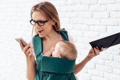 Telefono di conversazione agitato della donna di affari con neonato immagini stock libere da diritti