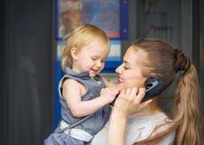 Telefono di conversazione del bambino e della madre in città Immagini Stock