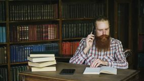 Telefono di conversazione del giovane studente barbuto mentre preparando per gli esami nella biblioteca di univercity Fotografia Stock
