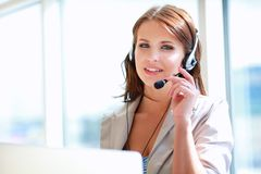 Telefono di conversazione della donna di affari mentre lavorando al suo computer all'ufficio Immagine Stock