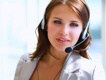 Telefono di conversazione della donna di affari mentre lavorando al suo computer all'ufficio Fotografia Stock