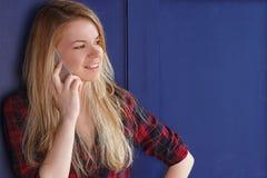 Telefono di conversazione sorridente della donna su fondo blu di legno Fotografia Stock