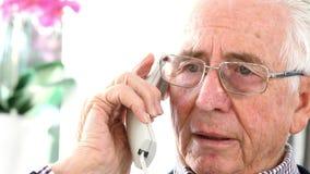 Telefono di risposta preoccupato dell'uomo senior a casa stock footage