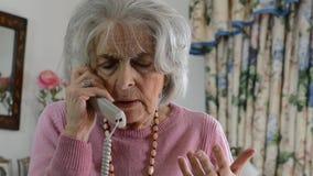 Telefono di risposta preoccupato della donna senior a casa archivi video