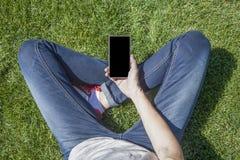 Telefono di schermo in bianco fornito di gambe su erba Immagini Stock