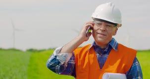 Telefono di Talking On Mobile dell'ingegnere mentre camminando nell'azienda agricola stock footage