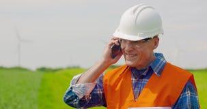 Telefono di Talking On Mobile dell'ingegnere mentre camminando nell'azienda agricola video d archivio