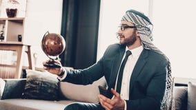 Telefono di tenuta arabo ed esaminare globo fotografia stock libera da diritti