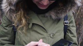 Telefono di uso della donna di bellezza felicemente sulla parete della pianta stock footage