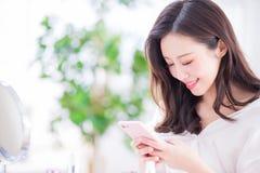 Telefono di uso della donna a casa fotografia stock
