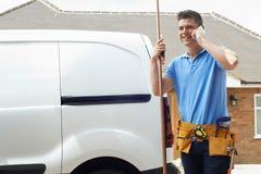 Telefono di With Van Making Call On Mobile dell'idraulico fuori della Camera Fotografie Stock Libere da Diritti
