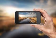 Telefono a disposizione e paesaggio Immagini Stock Libere da Diritti