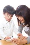 Telefono e genitore e bambino astuti Fotografia Stock