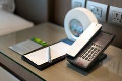 Telefono e nota neri nella parte anteriore ed in letto nei precedenti, foc fotografie stock libere da diritti