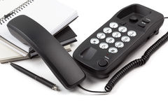 Telefono e pila presi di taccuini su fondo bianco Immagine Stock Libera da Diritti