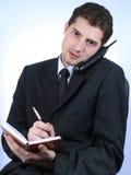 Telefono e scrittura dell'operaio impiegatizio Fotografia Stock