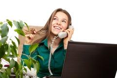 Telefono felice della donna nell'ufficio fotografie stock libere da diritti
