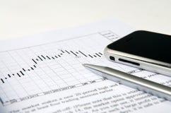 Telefono mobile con la penna sul diagramma di riserva Fotografia Stock