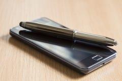 Telefono mobile e una penna fotografie stock libere da diritti