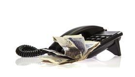 Telefono nero con la pila di soldi immagine stock