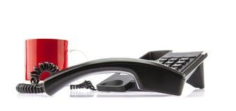 Telefono nero di affari con la tazza rossa fotografia stock