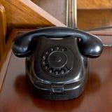 Telefono nero polveroso d'annata del vecchio disco sullo scrittorio Fotografie Stock