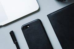 Telefono nero, taccuino nero e penna nera con il computer portatile d'argento sul piano d'appoggio, primo piano, vista superiore, immagine stock