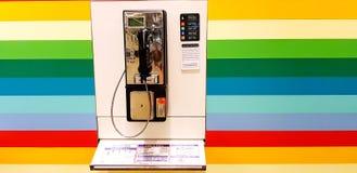 Telefono pubblico sui precedenti di colore dell'arcobaleno con lo spazio della copia all'aeroporto di Changi, Singapore immagini stock libere da diritti