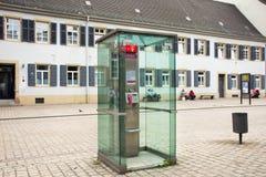 Telefono pubblico sulla via accanto alla strada di traffico in piccolo vicolo alla città di Speyer fotografia stock libera da diritti