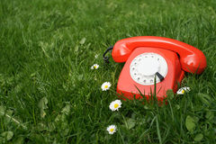 Telefono rosso all'aperto nell'erba Fotografia Stock