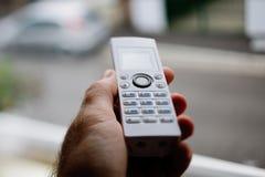 Telefono senza cordone a disposizione contro la finestra Immagini Stock Libere da Diritti