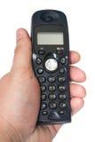 Telefono senza cordone nero nella mano sui precedenti bianchi Fotografia Stock