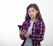 Telefono sorpreso della tenuta della ragazza su fondo bianco Studente con lo smartphone immagini stock libere da diritti