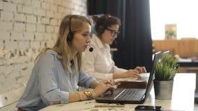 Telefono sorridente dell'operatore della call center della donna del gruppo di servizio di assistenza al cliente video d archivio