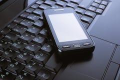 Telefono su un computer portatile Fotografia Stock Libera da Diritti
